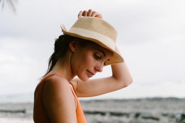 Portrait of woman in straw hat, sea background